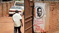 FILE - In this Thursday, Sept. 20, 2018 file photo, a man walks past graffiti in support of pop star-turned-opposition lawmaker…