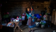 Alba Organiz holds her son Rudy Anibal while preparing food for guests who have come to pay their respects to the family of…