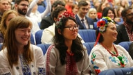 Volunteers of US Peace Corps wearing Ukrainian-style costumes smile at a ceremony of swearing an oath of allegiance in Kiev,…
