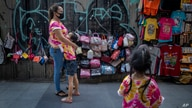 A child hugs her mother as a sibling watches at their sidewalk shop aimed for tourists in Bangkok, Thailand, Wednesday, July 29…