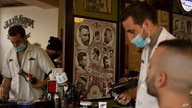 A barber gives a customer a haircut after coronavirus restrictions were eased, opening shopping centers, gyms, barber shops,…
