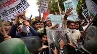 Security officers push back people shouting slogans during a protest held to show support to farmers who have been on a months…