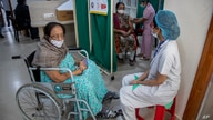 An elderly woman receives the COVID-19 vaccine as another waits in a wheelchair at a private hospital in Gauhati, India,…