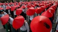 Anti-coup school teachers in their uniform and traditional Myanmar-hats participate in a demonstration in Mandalay, Myanmar,…