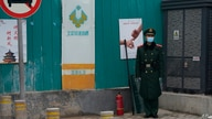 A paramilitary police officer stands guard in an area near the Great Hall of the People where delegates are attending the…