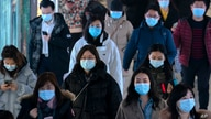 Commuters wearing face masks to protect against the spread of the coronavirus walk through a subway station in Beijing,…