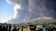 People watch as Mount Sinabung spews volcanic material during an eruption in Karo, North Sumatra, Indonesia, Tuesday, March 2,…