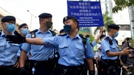 Police officers raise a warning flag against supporters gathered outside a court in Hong Kong Monday, March 1, 2021. Hong Kong…