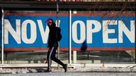 FILE - In this Feb. 25, 2021, file photo, a pedestrian in a face covering walks past the sign plastered on the windows of a…