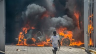 A boy runs out from the Nissan auto dealership set ablaze during a protest by a sector of the police force known as Fantom 509…