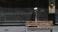 A cleric walks past a closed shop of Tehran's Grand Bazaar, Iran, Saturday, April 10, 2021. Iran on Saturday imposed partial…