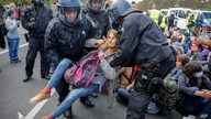 Police officers carry away a demonstrator after police stop a protest rally against the German government's policy to battle…