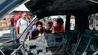Boy look at a damaged vehicle at the scene of an explosion at a crowded outdoor used furniture market in Sadr City area, Iraq,…