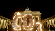 Activists of the environment organization Greenpeace protest with CO2 letters illuminated with flames in front of the…