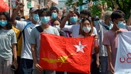 Anti-coup protesters hold the flag of the National League for Democracy party of ousted Myanmar leader Aung San Suu Kyi