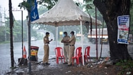 Policemen enforcing a lockdown to curb the spread of coronavirus stand beneath a rain shelter in Kochi, Kerala state, India,…