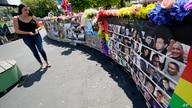 A visitor looks over a display with the photos and names of the 49 victims that died at the Pulse nightclub memorial Friday,…