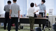 Employees of the beverage maker Suntory register to receive shots of the Moderna COVID-19 vaccine at their office building as…