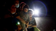 FILE - In this May 17, 2021, file photo a group of migrants mainly from Honduras and Nicaragua wait along a road after turning…