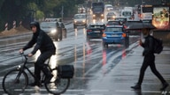 A cyclist and a passer-by with an umbrella cross a traffic light intersection during rainfall in Hamburg, Germany, Monday, June…