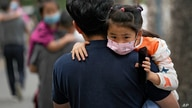 People carry their child wearing face masks to help curb the spread of the coronavirus head to a kindergarten in Beijing on…