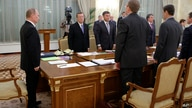 Russian Prime Minister Vladimir Putin, left, and the Cabinet stand during a minute of silence at a start of the Cabinet meeting…
