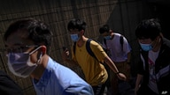 People wearing face masks to help curb the spread of the coronavirus walks out of an underpass tunnel as they head to work in…