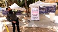 A private security guard gives directions to people looking to get vaccinated, as banners advertise the availability of the…