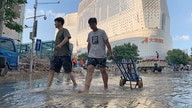 Residents walk along a flooded road in the aftermath of the heaviest recorded rainfall in Zhengzhou in central China's Henan…