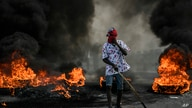 A protester demanding justice for the assassinated President Jovenel Moise stands near a burning barricade in Cap-Haitien,…