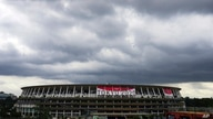 FILE - In this June 23, 2021, file photo, rain clouds move in over National Stadium, in Tokyo. Tens of thousands of visiting…