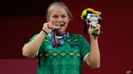 Polina Guryeva of Turkmekistan celebrates on the podium after winning the silver medal in the women's 59kg weightlifting event,…