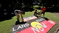 Protesters arrange signs in a social distanced crowd during an Aboriginal-lead Invasion Day rally on Australia Day in Sydney,…