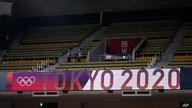 People walk through an empty section of spectator stands during judo competition at the 2020 Summer Olympics, Saturday, July 24…