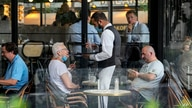 A waiter wearing a face mask to protect against coronavirus serves at a restaurant terrace in Paris, Monday, July 26, 2021…
