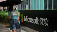 A woman wearing a face mask to help curb the spread of the coronavirus walks by the Microsoft office building in Beijing,…