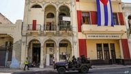 Special forces police patrol the streets as they drive past a large Cuban flag hanging from the facade of a building, in Havana…