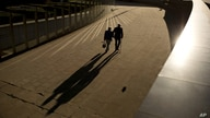 FILE - In this Thursday, Sept. 27, 2018 file photo, an elderly couple walks past the Berlaymont building, the European…