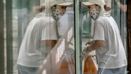 A delivery courier wearing a face mask to protect against COVID-19 is reflected in a window glass as she walks into a…