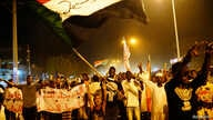 Sudanese people chant slogans and wave Sudanese flags during a demonstration in Khartoum.
