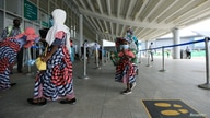 A family is seen in a  queue at the domestic wing of the Nnamdi Azikiwe International Airport on its re-opening day for domestic flight operations, following the coronavirus disease (COVID-19) outbreak, in Abuja
