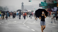 A woman wearing a mask walks past members of conservative civic groups who take part in an anti-government protest, as concerns over a fresh wave of the coronavirus disease (COVID-19) cases grow, in central Seoul