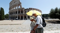 People walk past the Colosseum in Rome