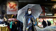 FILE PHOTO: An Iranian woman wears a protective face mask and gloves, amid fear of coronavirus disease (COVID-19), as she walks at Tajrish market, ahead of the Iranian New Year Nowruz, March 20, in Tehran
