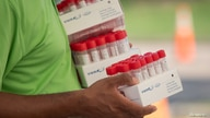 FILE PHOTO: Healthcare worker carries specimen collection tubes at COVID-19 drive-in testing location in Houston, Texas