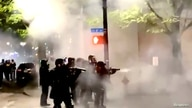 Police officers aim their weapons towards protesters demonstrating in Portland
