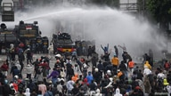 Police officers spray water using a canon to disperse demonstrators during a protest against the government's labour reforms in a polarising jobs creation bill in Jakarta