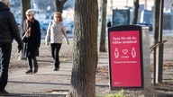 People strollIing in the cold but sunny weather pass a sign asking to maintain social distancing, amid the continuous spread of the coronavirus disease (COVID-19) pandemic, in Stockholm