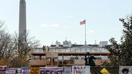 Workers construct viewing stands for the 2021 Inaugural Parade in front of the White House in Washington