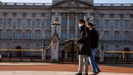 People wearing face masks walk past Buckingham Palace in London